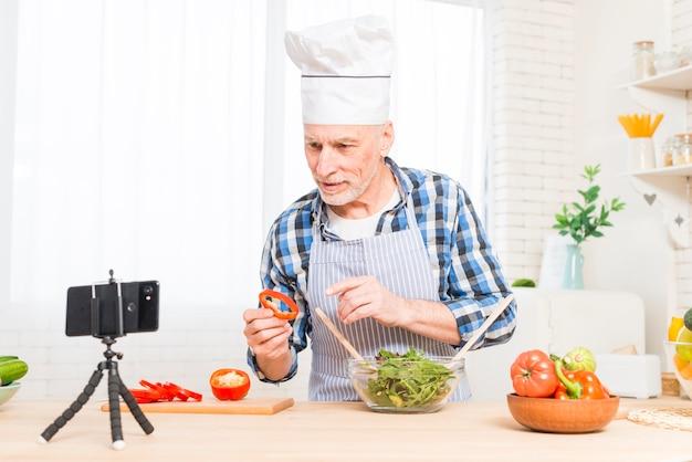 Tragender weißer chefhut des älteren mannes, der videoanruf beim kochen des lebensmittels in der küche macht