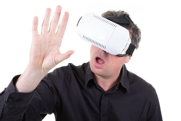 Tragender weißer kopfhörer der virtuellen realität des mannes, der großen spaß hat