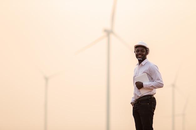 Tragender weißer schutzhelm des afrikanischen ingenieurs, der mit digitaler tablette gegen windkraftanlage am sonnigen tag steht