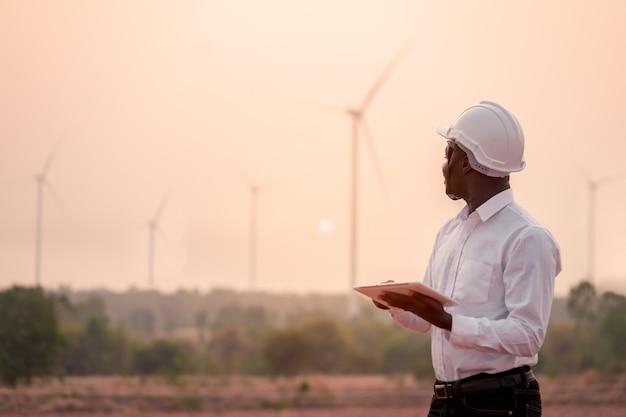 Tragender weißer schutzhelm des afrikanischen ingenieurs, der mit digitaler tablette gegen windkraftanlage steht