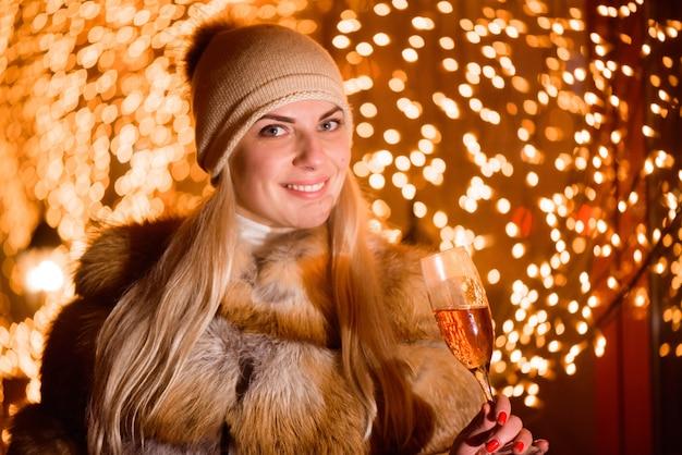 Tragender winterhut des mädchens mit glas champagner an der party über glühendem gold des feiertags