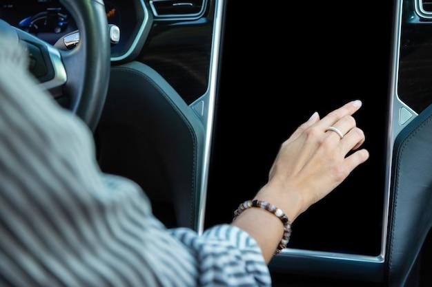 Tragendes armband der frau. nahaufnahme einer frau mit armband mit navigation im auto während der fahrt in