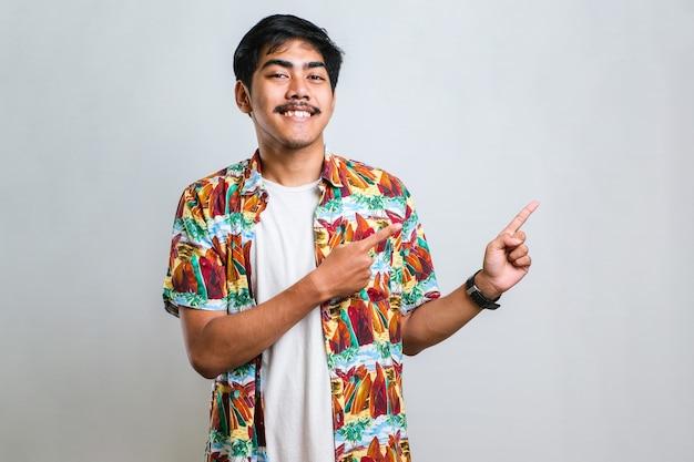 Tragendes beiläufiges hemd des jungen hübschen asiatischen mannes über weißem hintergrund mit einem großen lächeln auf gesicht; mit handfinger zur seite zeigend in die kamera schauend.