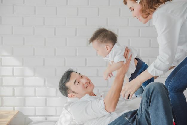 Tragendes kind des asiatischen japanischen familienvater-muttersohns des weißen hemdes auf schlafzimmer im reinraum.