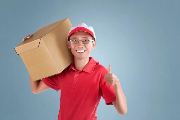 Tragendes paket des jungen asiatischen lieferers und sich zeigen daumen
