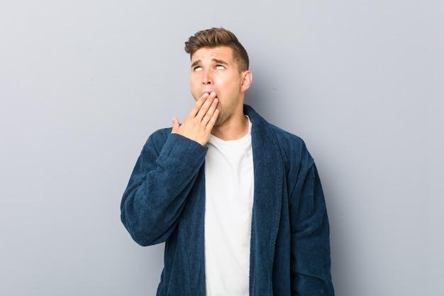 Tragendes pyjama des jungen kaukasischen mannes, das eine müde geste bedeckt mund mit der hand zeigend gähnt.