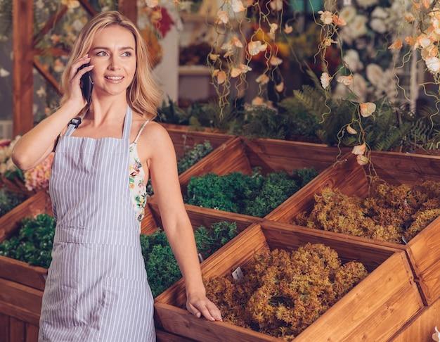 Tragendes schutzblech des floristen, das auf dem mobiltelefon steht vor hölzerner kiste spricht