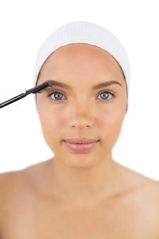 Tragendes stirnband der sinnlichen frau unter verwendung der augenbrauenbürste