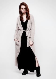 Tragendes strickwarenkleid des jungen schönen mode-modells und schwarzer rock auf grau