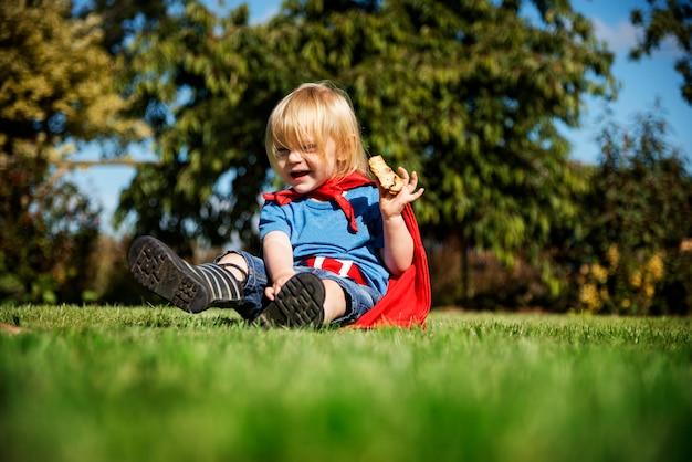 Tragendes superheldkostüm des kleinen jungen, das in einem park spielt