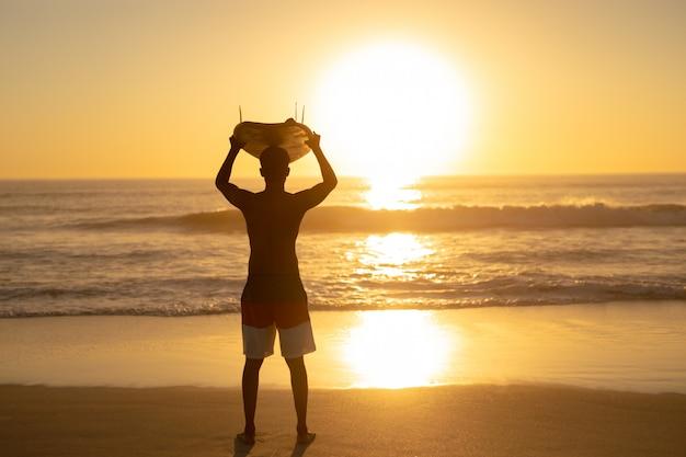 Tragendes surfbrett des mannes auf seinem kopf am strand