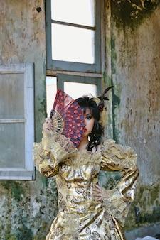 Tragendes victoriankostüm der chinesin, das einen fan, trieb am schmutzgebäude hält