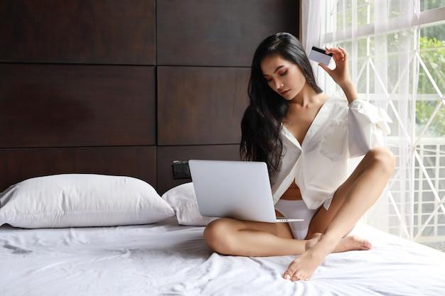 Tragendes weißes kleid der erwachsenen asiatischen sexy frau, das online auf computer mit kreditkarte beim sitzen auf bett im schlafzimmer kauft