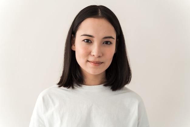 Tragendes weißes t-shirt des attraktiven asiatischen mädchens, das gerade in die kamera schaut. junge frau posiert auf einem weißen wandhintergrund