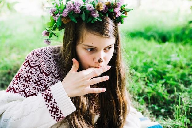 Tragendes wreathe des hübschen mädchens auf dem kopf, der ihre finger mit schokoladenfleck auf nase leckt