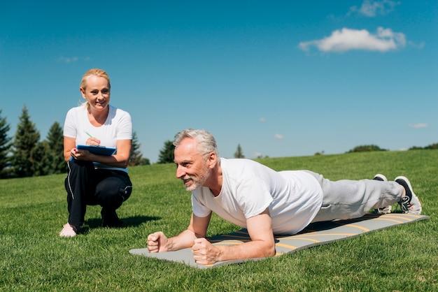 Trainer, der den plankenwiderstand des mannes misst