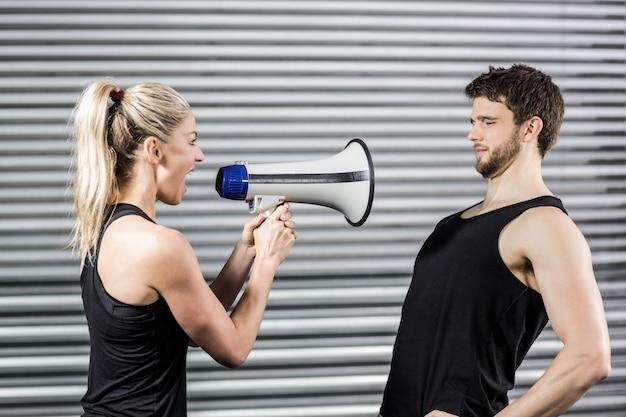 Trainer, der durch das megaphon am crossfit gym schreit