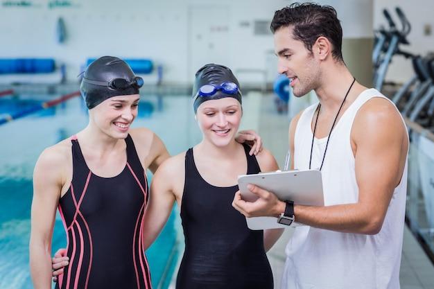 Trainer, der mit lächelnden schwimmern in der freizeitmitte spricht