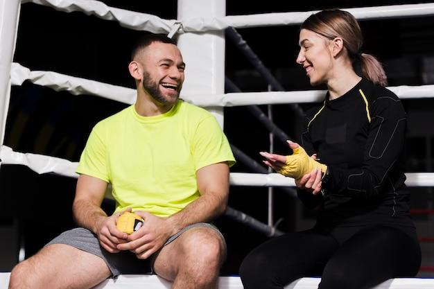 Trainer, der mit weiblichem boxer nahe bei ring plaudert