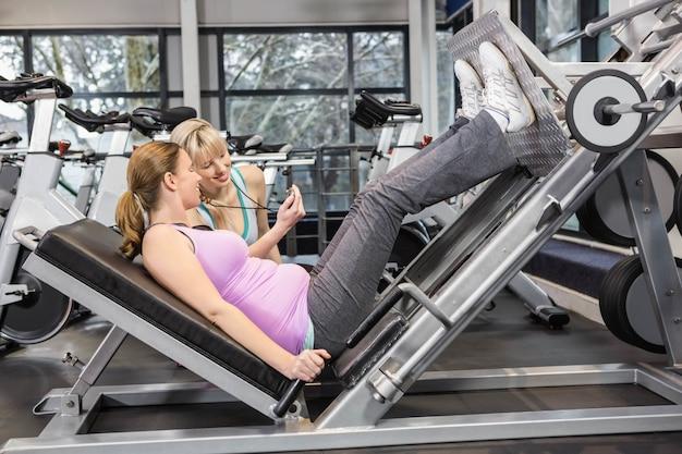 Trainer, der schwangere frau bei der anwendung der beinpresse an der turnhalle motiviert