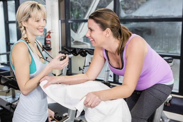 Trainer, der stoppuhr verwendet, während schwangere frau hometrainer an der turnhalle benutzt