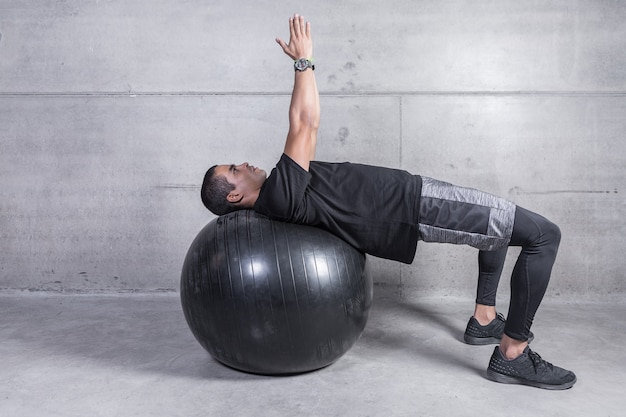 Trainer, der übung auf medizinball zeigt