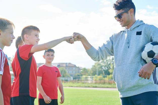 Trainer fistbumping junior team