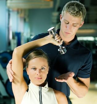 Trainer helfen mädchen mit einer übung hanteln