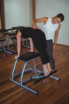 Trainer hilft einer frau beim üben von pilates