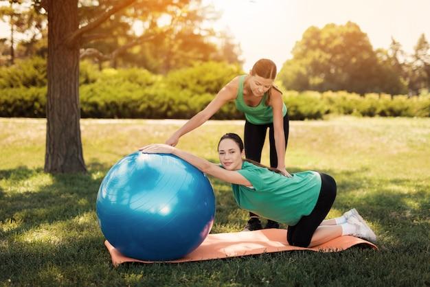 Trainer hilft einer frau in einem grünen t-shirt, das yogaübungen tut.
