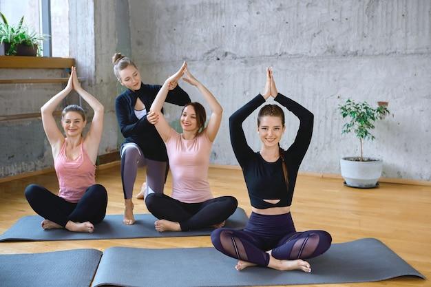 Trainer hilft frauen beim üben von meditation in der halle.