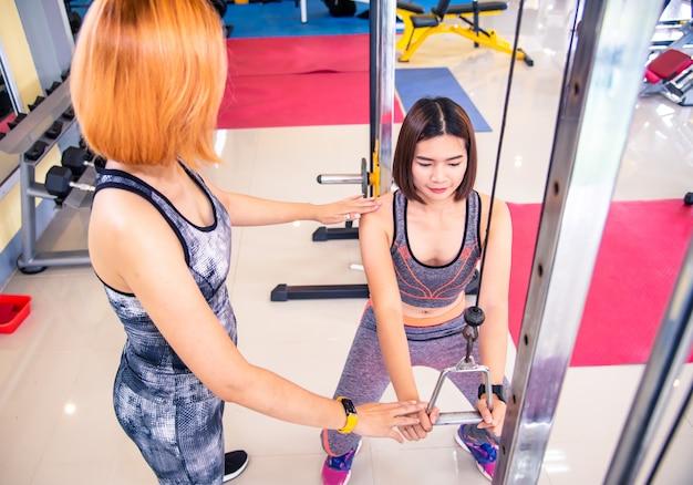 Trainer im fitnessstudio kümmern sich um die mitglieder des fitnessstudios.