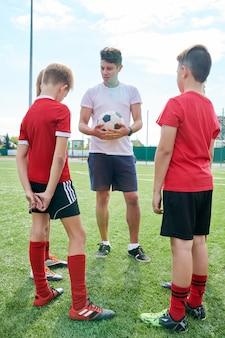 Trainer im gespräch mit der junioren-fußballmannschaft