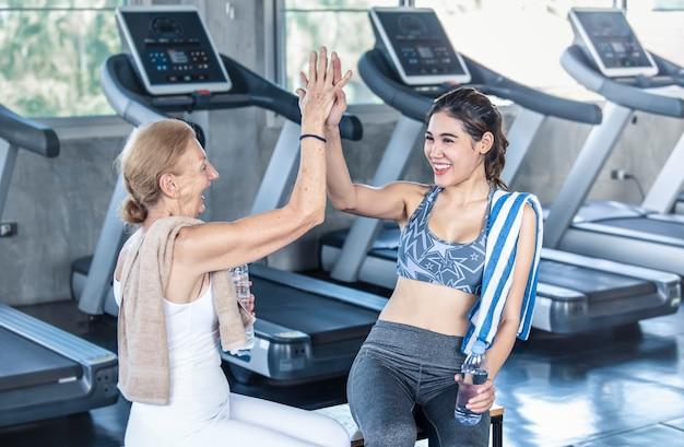 Trainer mit der älteren frau, die highfive in der eignungsturnhalle gibt. älteres gesundes lebensstilkonzept.