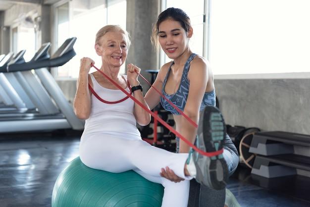 Trainer mit der älteren frau, die übung in der turnhalle ausdehnt. älterer gesunder lebensstil und trainingskonzept.