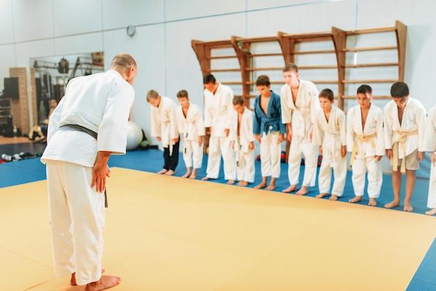 Trainer und kinder in uniform, kinderjudotraining. junge kämpfer in turnhalle, kampfkunst, gesundheitslebensstil