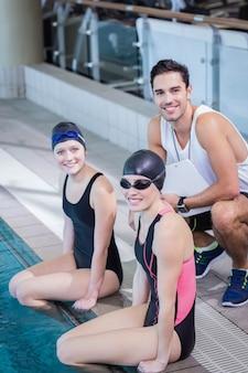 Trainer und schwimmer, die in die kamera im freizeitzentrum lächeln