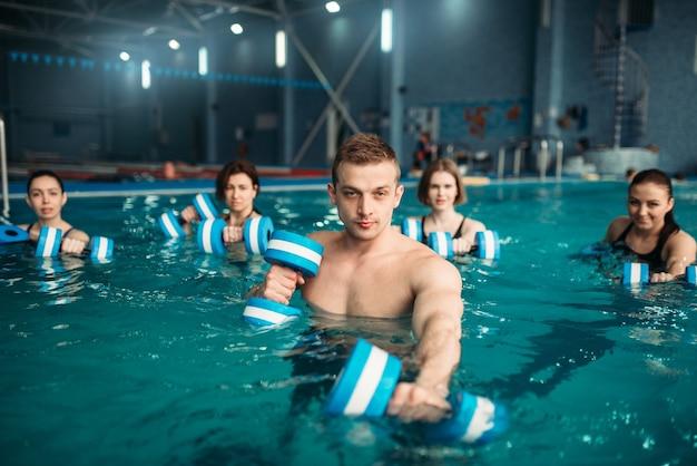 Trainer und weibliche aqua-aerobic-gruppe, übung mit hanteln beim training im schwimmbad. fitnesstraining, wassersport