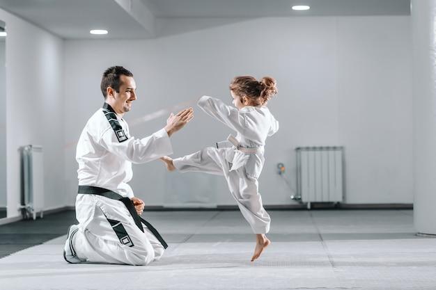 Trainer unterrichtet mädchen taekwondo,