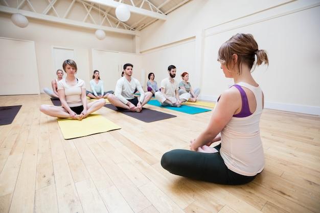Trainer unterstützen gruppe von menschen in der meditation