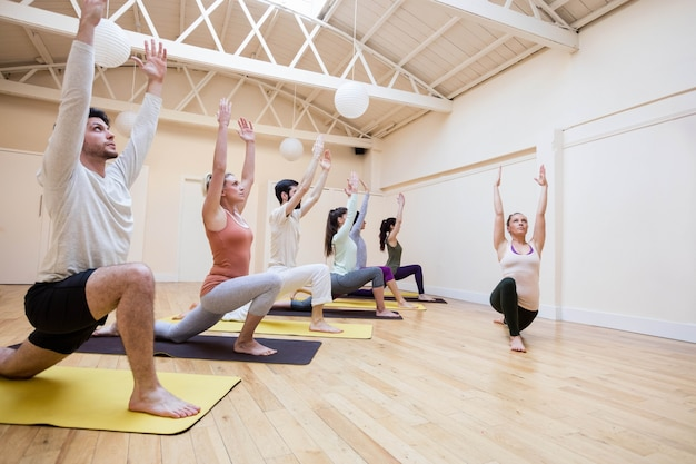 Trainer unterstützen gruppe von menschen mit krieger-pose auf übung