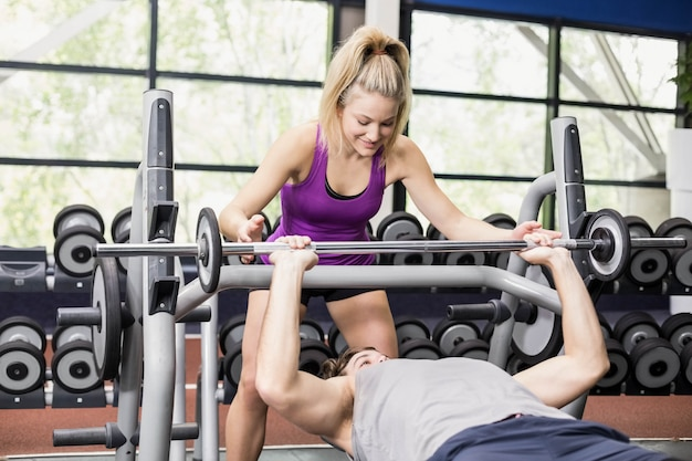 Trainerfrau, die athletischem mann an crossfit turnhalle hilft