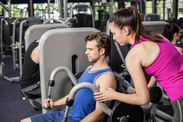 Trainerfrau, die athletischem mann in der turnhalle hilft