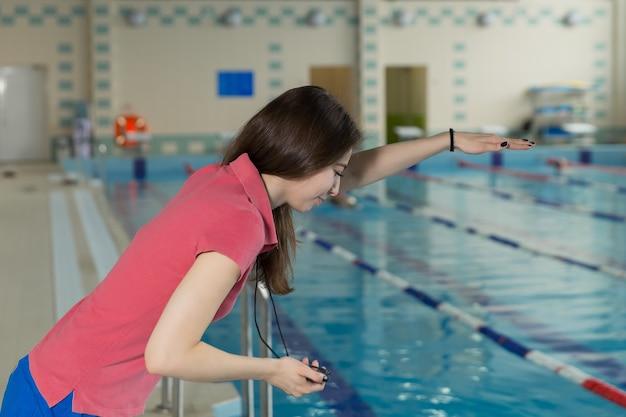 Trainerfrau, die eine stoppuhr am pool hält und training durchführt.