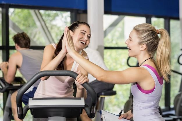 Trainerfrau und sportlerin, die an der turnhalle high-fiving sind