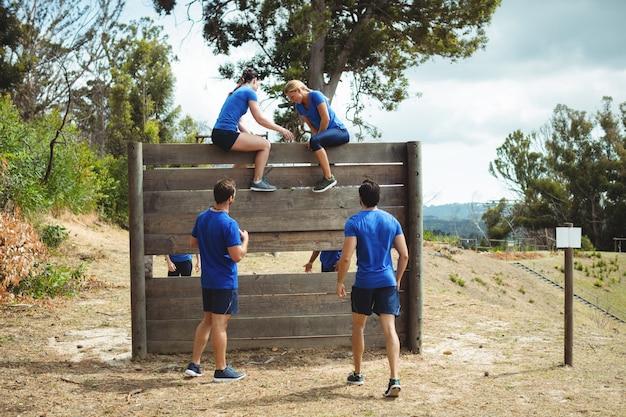 Trainerin, die fitte frau hilft, über holzwand während des hindernislaufs zu klettern