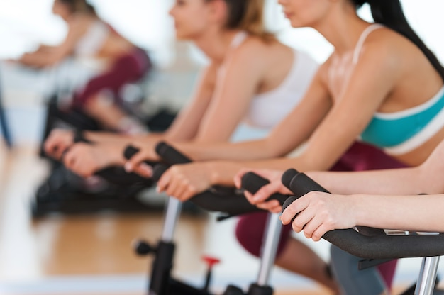 Trainieren auf fitnessrädern. abgeschnittenes bild von jungen frauen des baumes in sportkleidung