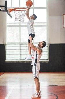 Trainieren. ein trainer hält einen jungen an den schultern, während er den ball in den ring wirft