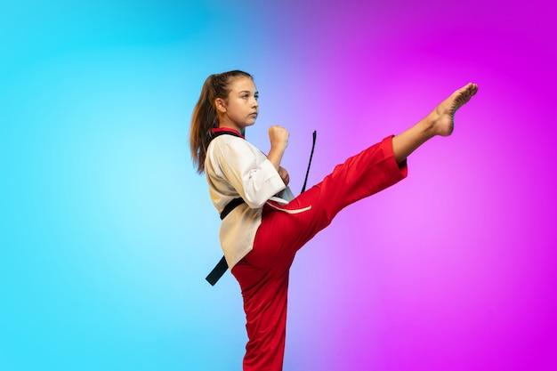 Trainieren. karate, taekwondo-mädchen mit schwarzem gürtel einzeln auf farbverlaufshintergrund im neonlicht. kleines kaukasisches modell, sportkindertraining in bewegung und aktion. sport, bewegung, kindheitskonzept.
