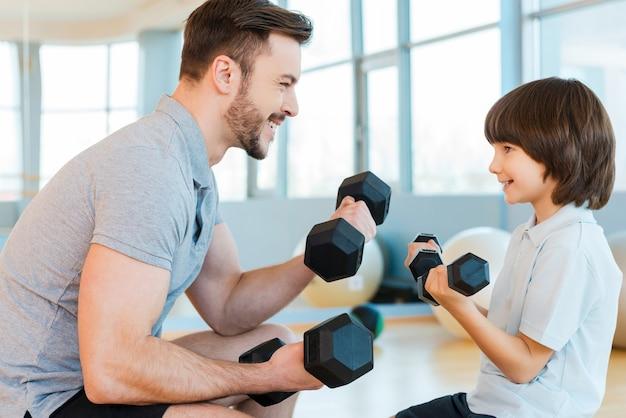 Trainieren macht spaß. glücklicher vater und sohn, die mit hanteln trainieren und lächeln, während sie beide im fitnessclub stehen